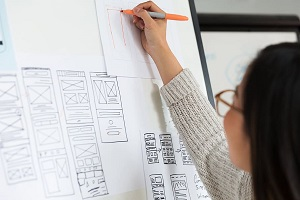 Woman making sketches and designing a mobile app development
