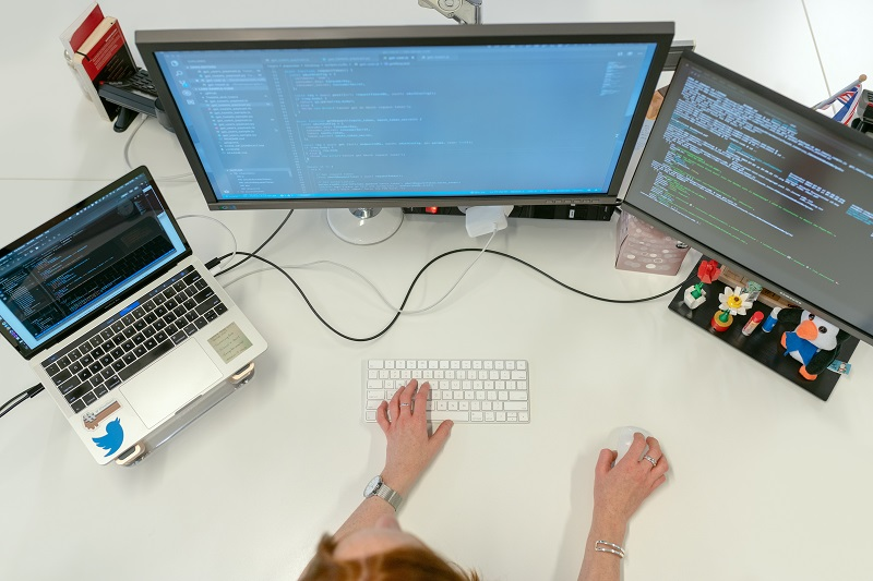woman working in three computers typind code