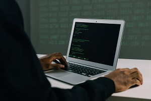 Black man working in his laptop writing code