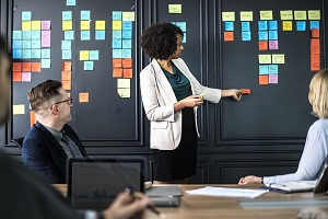 Three people having a meeting and watching a board of tasks