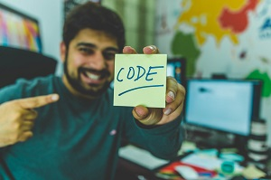 A man holding a paper with the the word code written on it