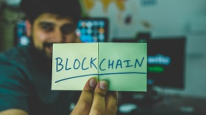 Young developer showing a paper with the word blockchain written on it