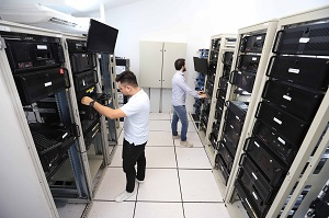 Two engineers working in a database room