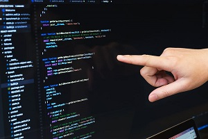 one hand pointing out a screen with code